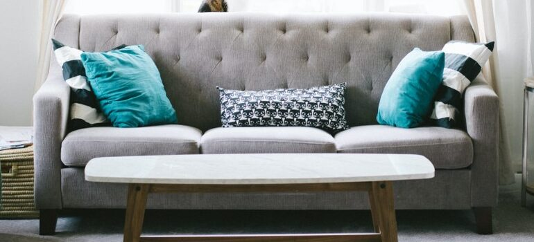 gray couch with pillows on, a small white table in front of the couch