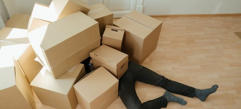 Man laying on the floor covered with the bunch of boxes.