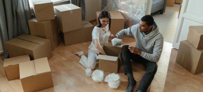 a couple sitting in their living room with boxes all around them