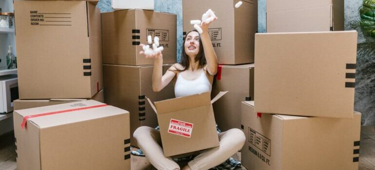 Girl sitting in front of cardboard boxes playing with styrofoam balls.