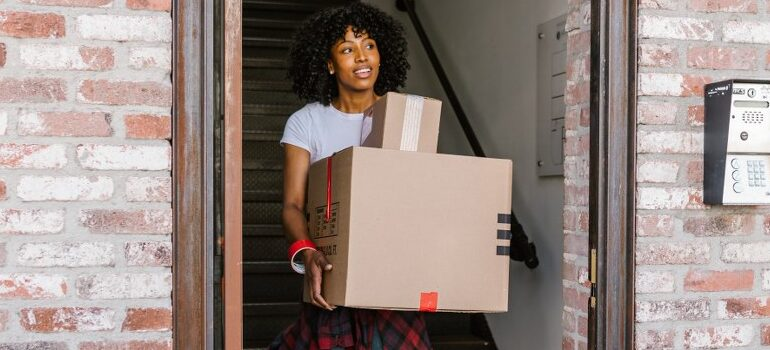 woman carrying two cardboard boxes