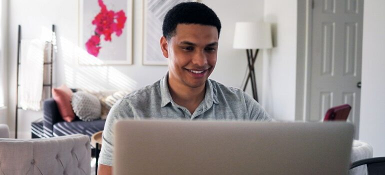 person looking at a laptop screen, smiling