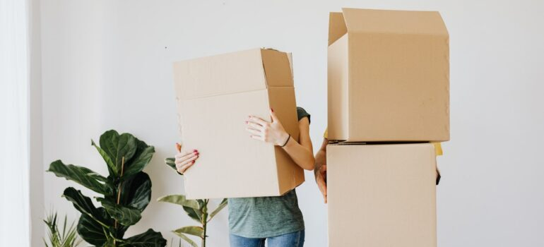 Two people holding cardboard boxes.