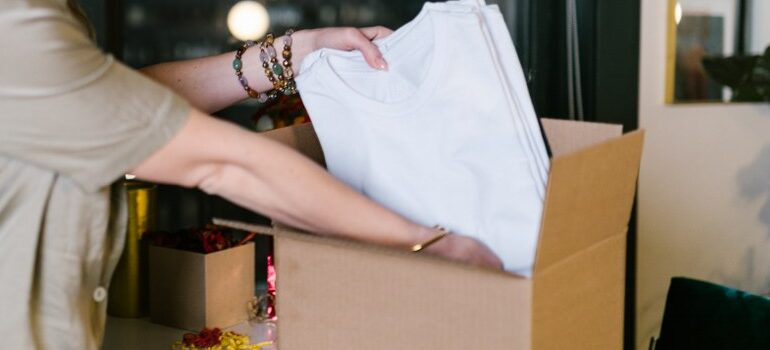 person packing a shirt in a box