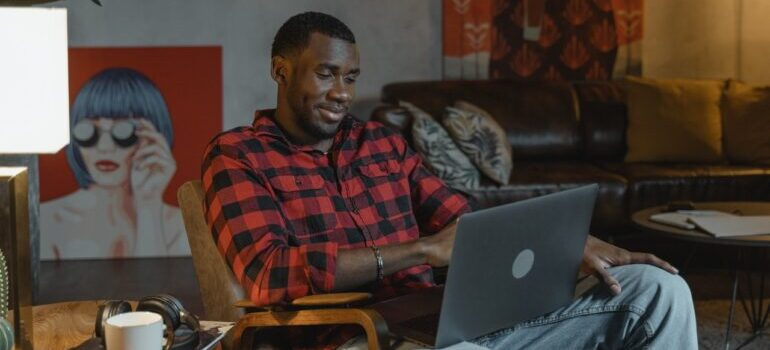 A man in a plaid shirt using laptop to find best cross country movers Topeka.